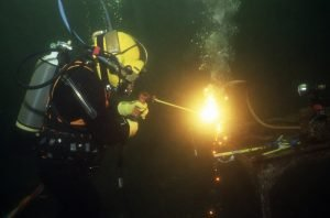 A commercial diver cutting through metal